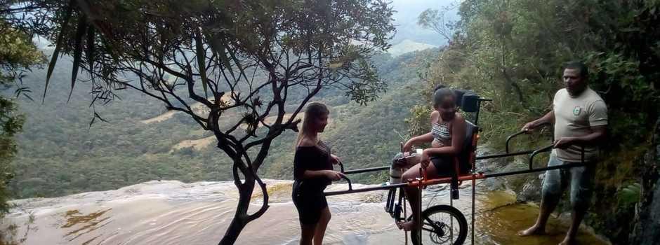 A jovem Tauana realizou um sonho ao chegar na Janela do Céu com apoio dos funcionários do Ibitipoca e de familiares; Cadeiras adaptadas possibilitam a pessoas com mobilidade reduzida acesso às atrações da reserva - Foto: IEF/divulgação