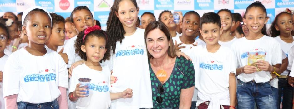 A presidente do Servas, Alexia Paiva, ao lado das crianças que assistiram ao espetáculo