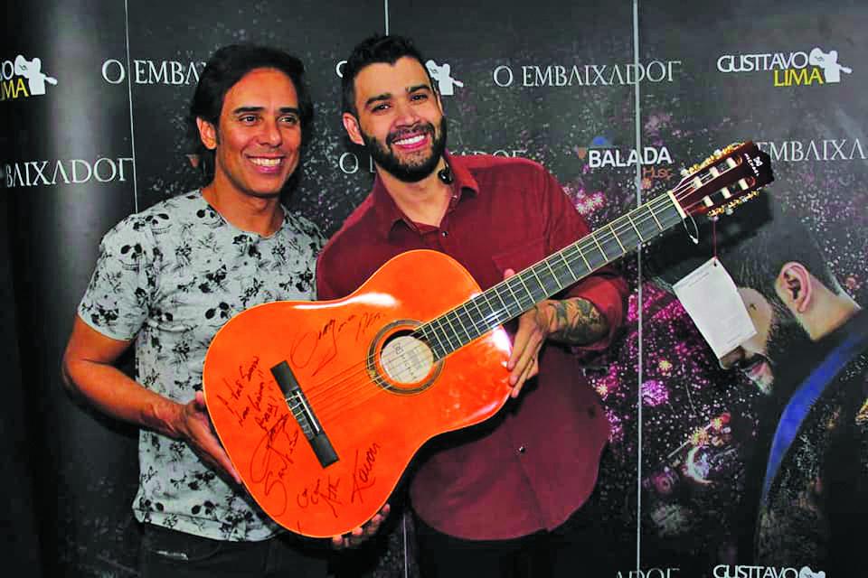 Gusttavo Lima convidou o amigo Guilherme para registrar o momento com o violão que será leiloado com renda para o Hospital do Câncer de Uberaba